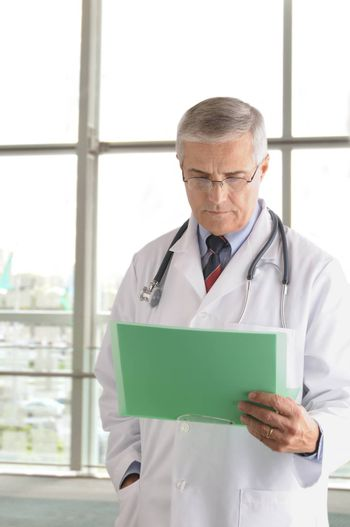 Middle aged doctor reading chart in front of the window of a  modern medical facility