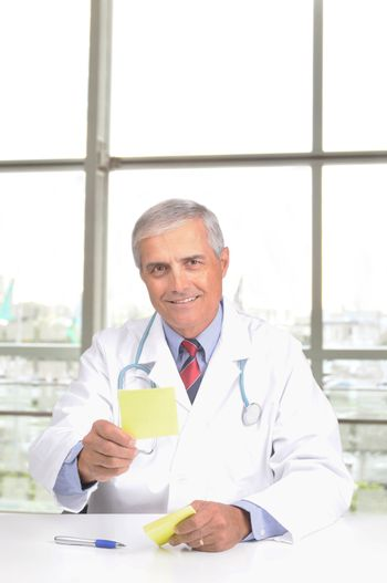 Middle Aged Male Doctor in Lab Coat with Stethoscope and Prescription Pad in modern office setting vertical format