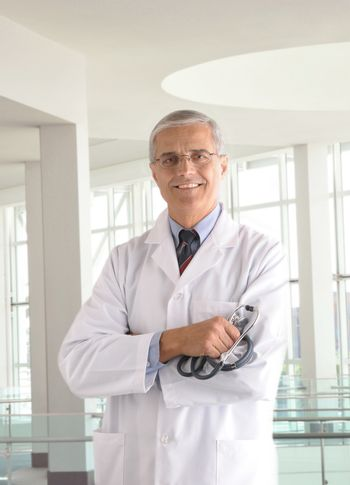 Middle aged doctor holding stethoscope with arms crossed in modern medical facility
