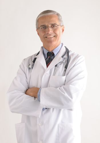Middle Aged Doctor in Lab Coat with Arms Folded vertical format over gray background