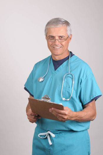 Smiling Middle Aged  Doctor in Scrubs Reading a Patients cart on his clipboard