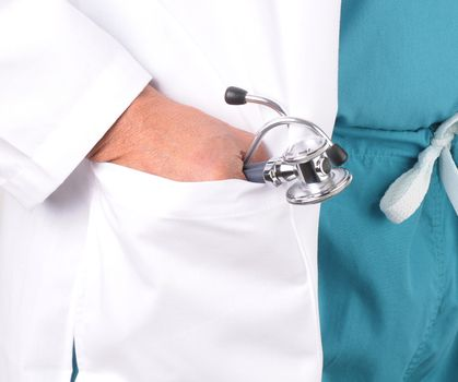 Close-up of a male doctors hand in his lab coat pocket holding on to a stethoscope. Doctor is wearing green scrubs.