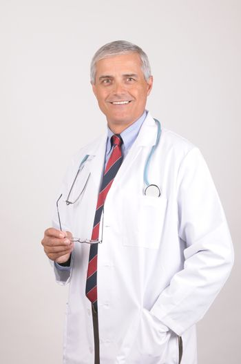 Smiling Middle Aged  Male Doctor in Lab Coat with Stethoscope Holding his eye glasses- gray background
