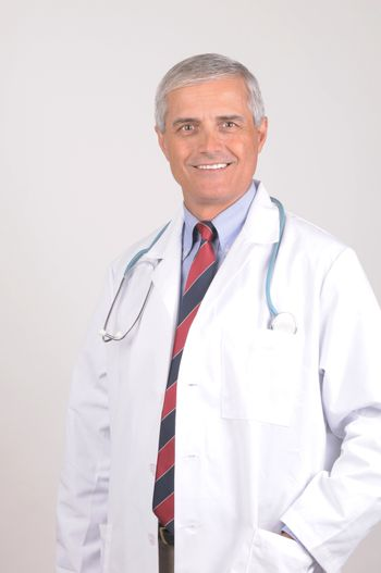 Smiling Middle Aged  Male Doctor in Lab Coat with Stethoscope - gray background
