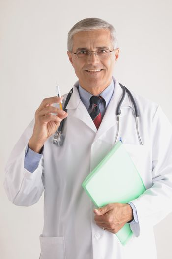 Middle Aged Doctor in Labcoat with Syringe and  Stethoscope and Chart vertical format