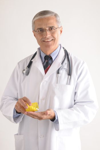Middle Aged Doctor in Labcoat Pouring Pills into His Hand vertical composition on gray background