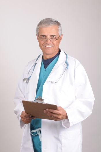 Smiling Middle Aged  Doctor in Scrubs and Lab Coat with clipboard -vertical composition on gray background