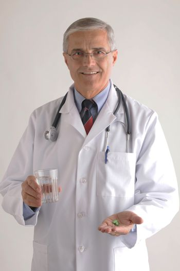 Middle Aged  Smiling Doctor in Labcoat with Pills and Glass of Water vertical format over light gray background