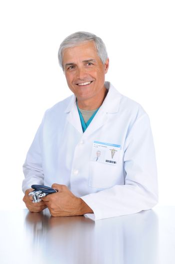 Smiling middle aged doctor seated and holding his stethoscope in both hands. Man is wearing a lab coat and scrubs in vertical format over a white background.