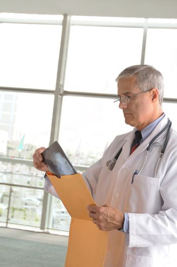 Middle aged doctor wearing lab coat looking at an xray in modern medical facility