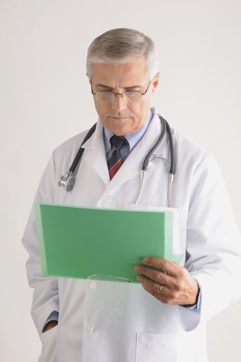 Middle Aged  Doctor in Lab Coat and Stethoscope Looking at a Patients Chart vertical format over gray background