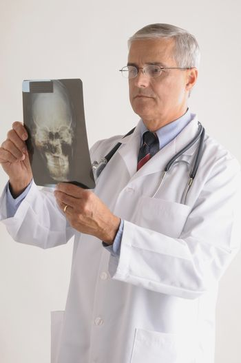 Middle Aged  Doctor in Lab Coat Looking at an X-Ray of a Skull