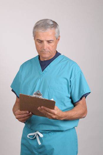 Middle Aged  Doctor in Scrubs Reading a Patients cart on his clipboard