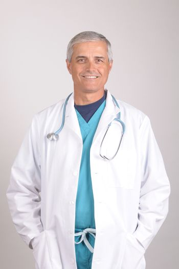 Smiling Middle Aged  Doctor wearing scrubs with his hands in the pockets of Lab Coat