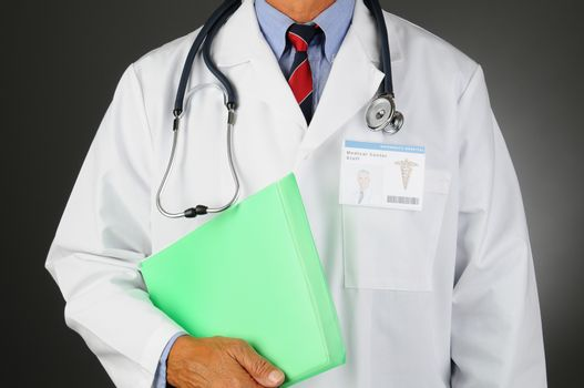 Closeup of a Middle Aged Medical Professional with a stethoscope around his neck holding a patients files. Man is unrecognizable, Id Badge shows his picture. Horizontal  on a light to dark background.