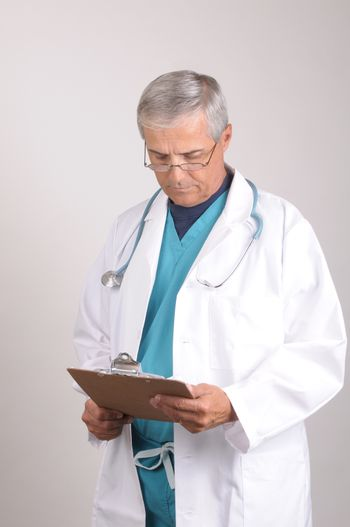 Middle Aged  Doctor in Scrubs and Lab Coat Reading chart on clipboard -vertical composition on gray background