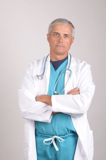 Serious Middle Aged  Doctor in Scrubs and Lab Coat with arms crossed - vertical on gray background