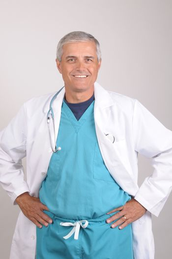 Smiling Middle Aged  Doctor wearing scrubs and lab coat with his hands on his hips