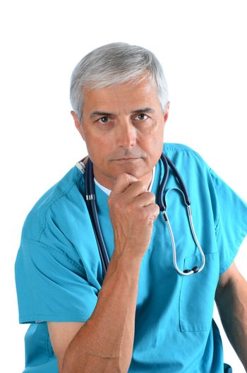 Serious middle aged doctor with his hand on his chin, Man is wearing scrubs with a stethoscope around his neck. Vertical Format over white.