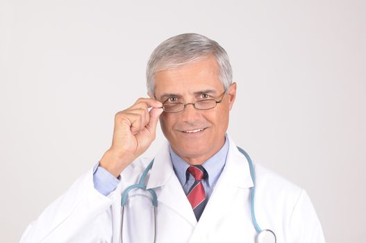 Portrait of a Middle Aged  Male Doctor in Lab Coat with Stethoscope adjusting his eye glasses - gray background