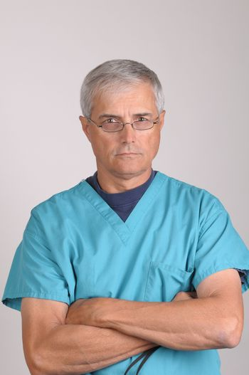 Middle Aged  Doctor in Scrubs with stern expression and his arms folded - vertical on Gray Background