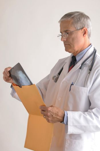 Middle Aged  Doctor in Lab Coat Removing an X-Ray from a large envelope