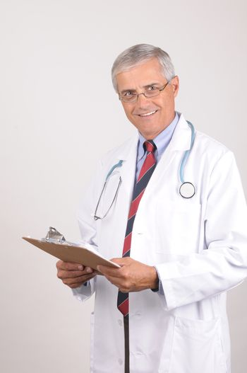 Portrait of a Middle Aged  Male Doctor in Lab Coat with Stethoscope and Clip Board, Vertical Composition on Gray Background