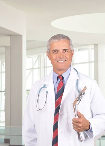 Middle Aged Doctor Holding Clipboard in Modern Medical Facility Setting vertical