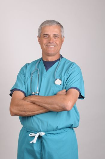 Middle Aged  Doctor in Scrubs with his arms folded over gray background vertical composition