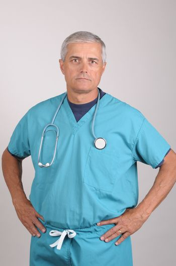 Serious Middle Aged  Doctor in Scrubs with Hands on Hips vertical on gray background