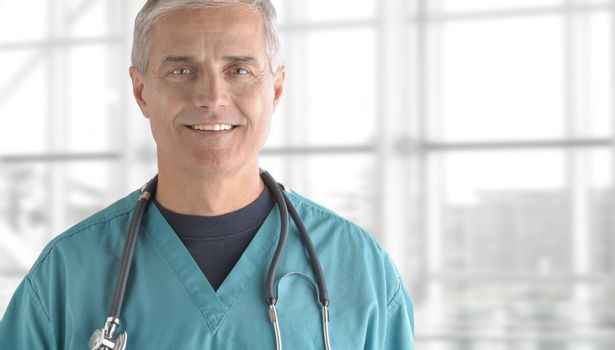 Portrait of smiling senior doctor standing against office window background while looking at camera.