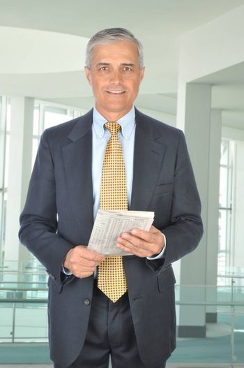 Standing Middle aged Businessman with Financial Section of Newspaper in modern office setting