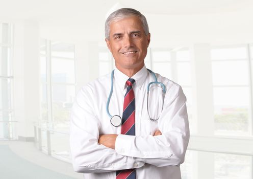 Smiling male doctor in scrubs with a stethoscope around his neck and his arms crossed. Vertical format torso view with high key background.