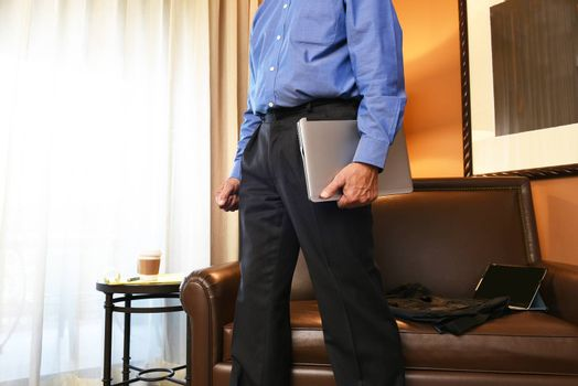 Closeup of a businessman walking in his hotel room carrying his laptop computer. Business travel concept.