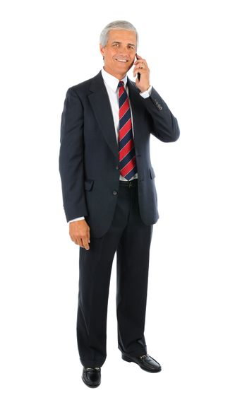 Smiling middle aged businessman in a suit and tie standing and talking on a cell phone with his other buy his side. Full length over a white background.