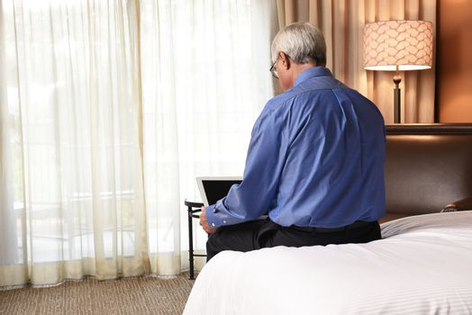 Business Travel Concept: Businessman sitting on the bed in his hotel room using his laptop computer. The mature man is seen from behind.