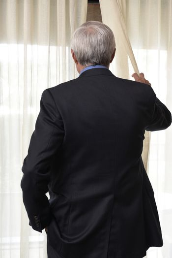 Closeup of a man seen from behind pulling back the drapes and peeking out a window.