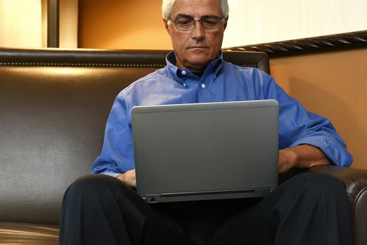 A senior businessman seated on a sofa in his hotel room and working on his laptop computer.