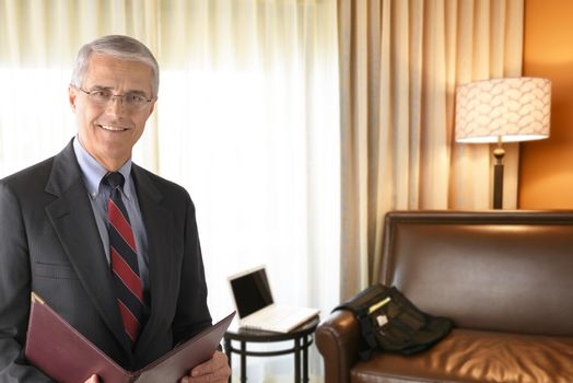 Portrait of a mature businessman in a hotel room holding a folder. Business travel concept.