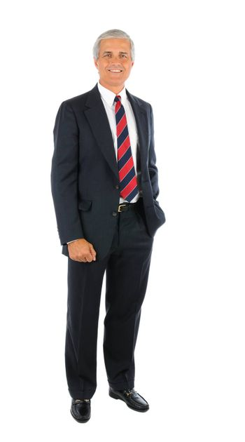 Smiling middle aged businessman in a suit and tie standing with one hand in his pocket and the other buy his side. Full length over a white background.