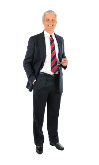 Smiling middle aged businessman wearing a suit standing with one hand in his pocket and the other holding his eye glasses. Full length over a white background.