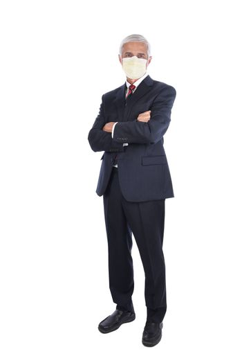 A businessman standing with his arm folded while wearing a protective mask, Isolated on white.