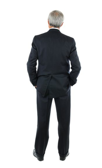 Standing middle aged businessman with both hands in his pockets. Full length shot of the mans back over a white background.