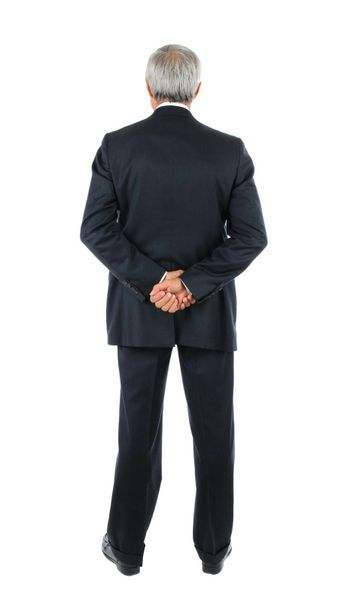 Standing middle aged businessman with both hands behind his back. Full length shot of the mans back over a white background.