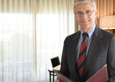 Business Travel Concept: Businessman in hotel room with folder.