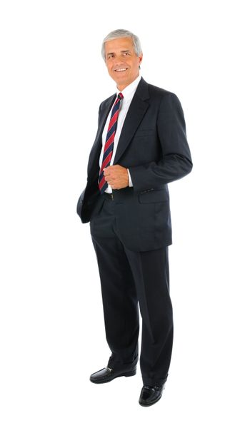 Smiling middle aged businessman in a suit and tie standing with one hand in his pocket. Full length over a white background.
