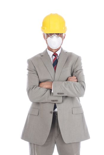 A businessman architect in a light tan suit wearing a hard had and protective face mask.