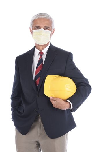 A builder or architect holding a yellow hard hat under his arm while wearing a protective mask, Isolated on white.