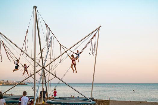 kids having fun on mini bungee jumping on the beach