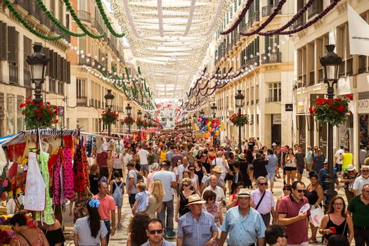 Malaga, Spain - August 12, 2018. People having fun on the Old street around the historic center at the Feria de Malaga, an annual event that takes place in mid-August and is one of the largest fiestas in Spain